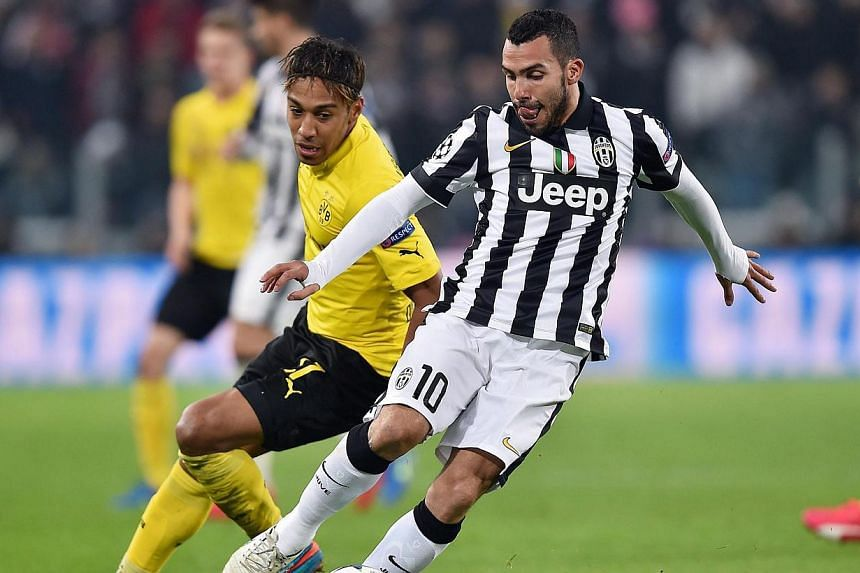 Juventus' Carlos Tevez (right) and Borussia Dortmund's Pierre-Emmerick Aubameyang in action during the UEFA Champions League Round of 16, first leg soccer match between Juventus Turin and Borussia Dortmund at the Juventus Stadium in Turin, Italy, Feb