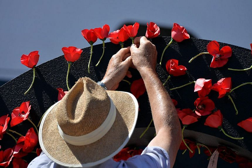 A visitor pays his respect to Australia's Anzac soldiers as he pins a poppy to the Wall of Remembrance in front of the Queen Elizabeth cruise ship in Sydney on March 3, 2015. Red poppies were placed on the Wall of Remembrance for each of the 11,500 A