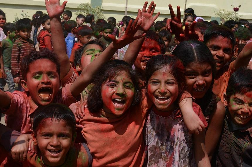 Indian children from the Bright Academy pose, after splashing each other with coloured powder known as gulal, as they celebrate the Holi festival in Siliguri on March 4, 2015. -- PHOTO: AFP