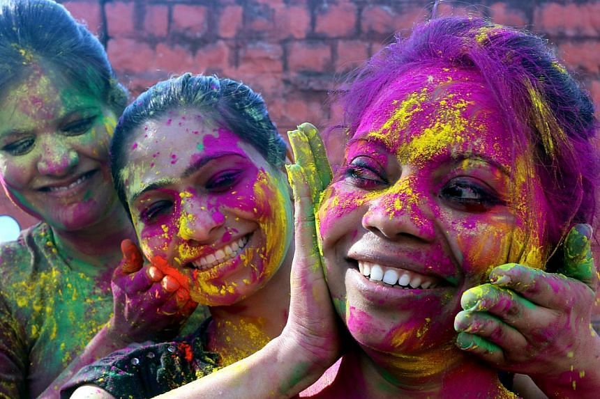Students put coloured powder on each other as they celebrate the Holi festival in Bhopal, India, on March 4, 2015. -- PHOTO: EPA