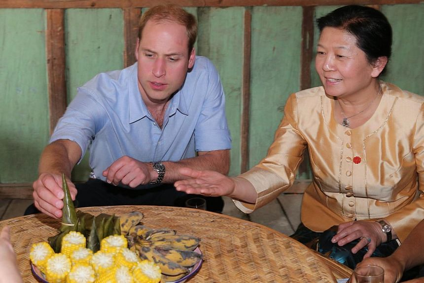 Britain's Prince William (left) visits a local villager's home in Xishuangbanna, or Sibsongbanna Dai autonomous prefecture, south-west China's Yunnan province on March 4, 2015. -- PHOTO: AFP