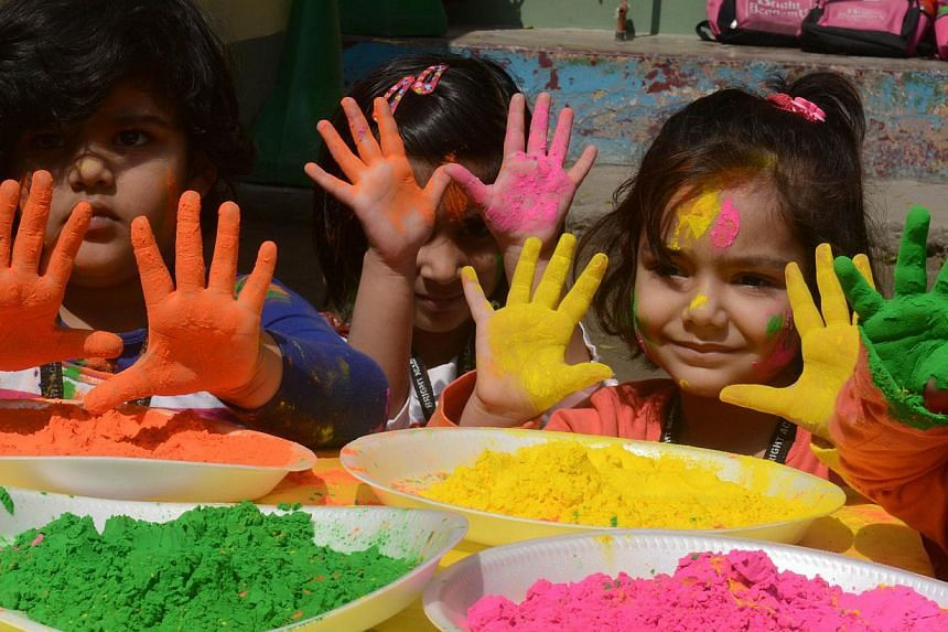 Indian children from the Bright Academy pose with coloured powder known as gulal used during the Holi festival in Siliguri on March 4, 2015. -- PHOTO: AFP