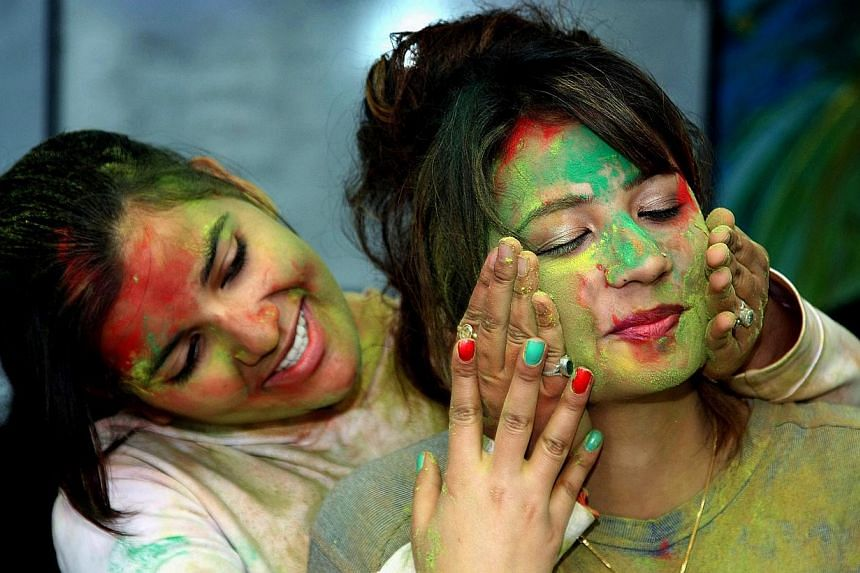 Indian college students put powdered colour on each other's faces as they participate in the Holi festival in Jammu, the winter capital of Kashmir, India, on March 4, 2015. -- PHOTO: EPA