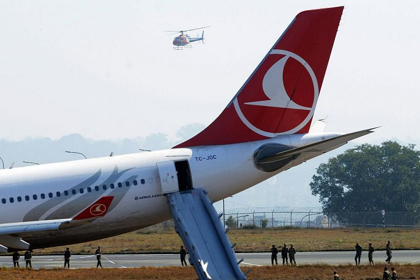 Nepalese rescue workers checking the area around a Turkish Airlines aircraft after it slid off the tarmac on landing at Kathmandu's Tribhuvan International Airporton March 4, 2015. -- PHOTO: AFP