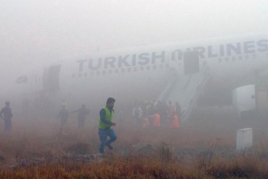 Passengers leaving a Turkish Airlines plane which skidded off the runway on landing at Kathmandu'sTribhuvan International Airporton March 4, 2015.-- PHOTO: AFP