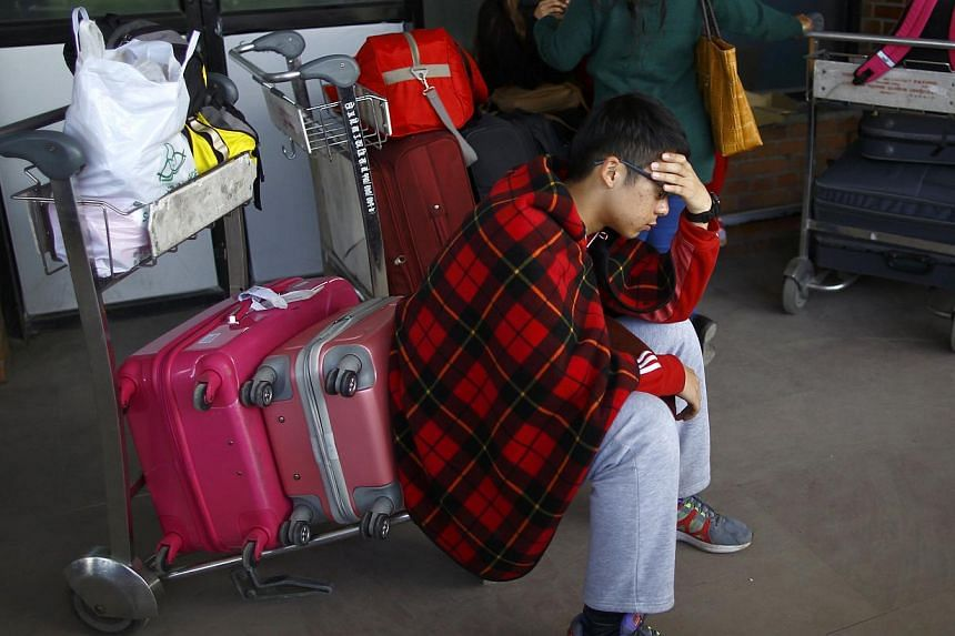 A stranded passenger waits at Tribhuvan International Airport following the airport's closure after a Turkish Airlines plane overshot a runway in Kathmandu on March 4, 2015. -- PHOTO: REUTERS