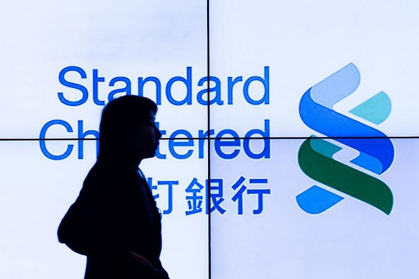 A woman walks past an electronic board displaying the logo of the Standard Chartered bank in Hong Kong on March 4, 2015.Standard Chartered ruled out plans to raise capital on Wednesday despite reporting a 25 per cent slide in annual pretax prof