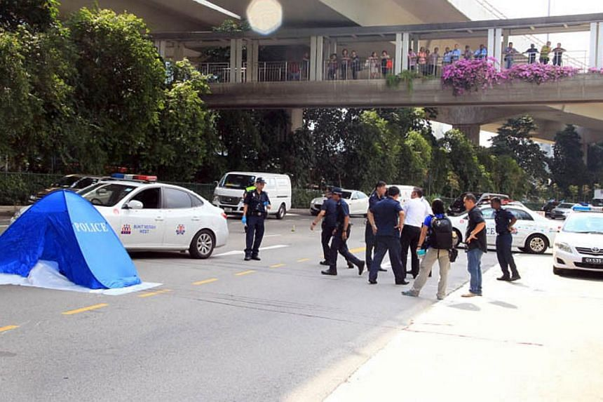 Police officers at the scene where a Vietnamese woman fell from the West Coast Highway on Tuesday afternoon. She was believed to have got off the motorcycle she was on, before leaping off the expressway.-- PHOTO:LIANHE WANBAO