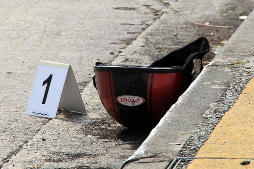 A motorcycle helmet is seenat the scene where a Vietnamese woman fell from the West Coast Highway on Tuesday afternoon.-- PHOTO:LIANHE WANBAO