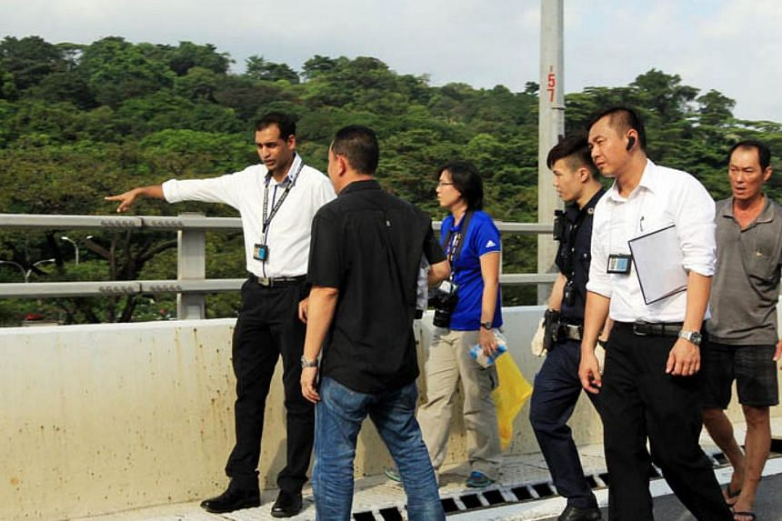 Police investigators on the West Coast Highway. A Vietnamese woman fell from the expressway on Tuesday afternoon.-- PHOTO:LIANHE WANBAO