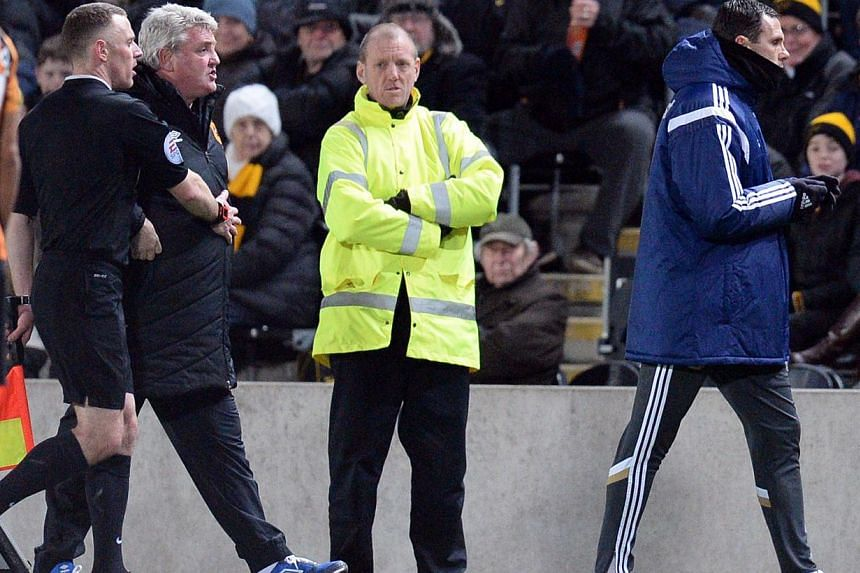 Hull City's English manager Steve Bruce (second from left) is held back as Sunderland's Uruguayan manager Gus Poyet (right) is sent to the stands on Mar 3, 2015. -- PHOTO: AFP
