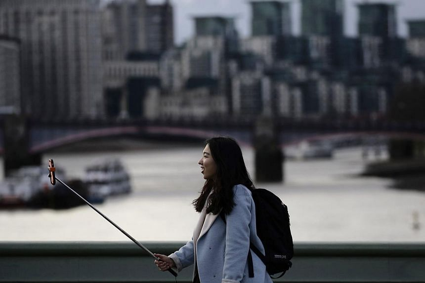 A woman taking a photo using a selfie stick. Washington's top museums say selfie sticks are banned, in a growing trend among visitor centres in the United States to outlaw the devices. -- PHOTO: REUTERS
