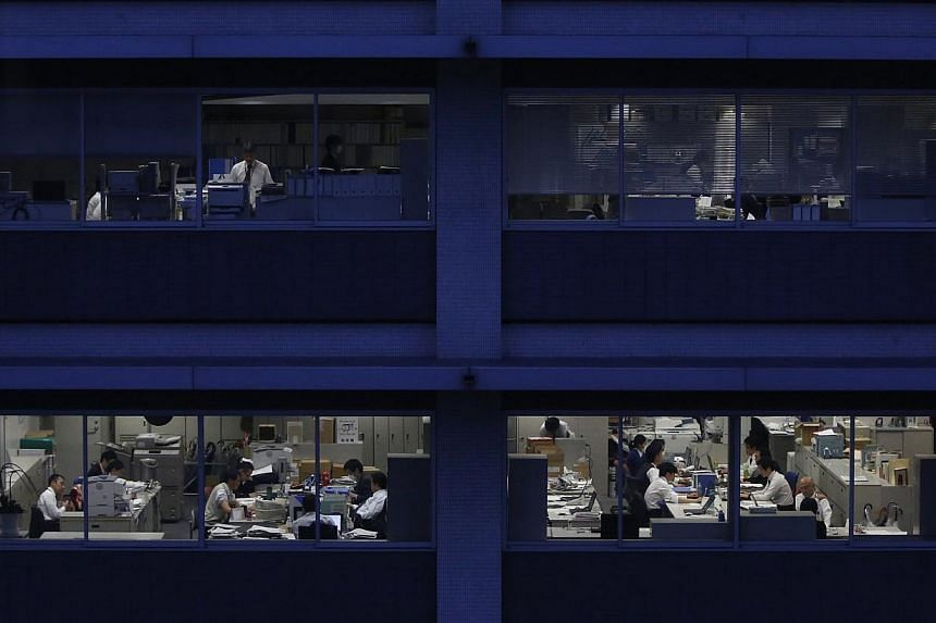 Officer workers are pictured through building windows during dusk in Tokyo on Mar 3, 2015.Millions of Japanese workers are taking home their smallest share of corporate income in two decades as companies build record cash hoards and abstain fro