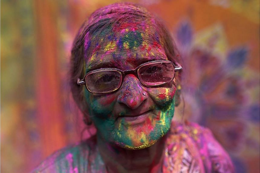 A widow daubed in colours takes part in Holi celebrations at Vrindavan, in the northern Indian state of Uttar Pradesh on March 3, 2015. -- PHOTO: REUTERS