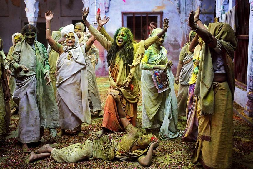 Widows daubed in colours chant religious hymns as they dance during the Holi celebrations at a widows' ashram at Vrindavan in the northern Indian state of Uttar Pradesh on March 4, 2015. -- PHOTO: REUTERS
