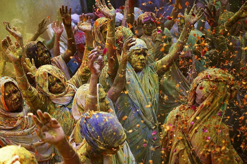 Widows daubed in colours chant religious hymns as they dance during the Holi celebrations at Vrindavan in the northern Indian state of Uttar Pradesh on March 4, 2015. -- PHOTO: REUTERS