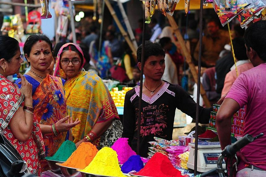 Indian women purchase colored powder for the 'holi' celebrations at a roadside stall in the old city of Allahabad on March 4, 2015. -- PHOTO: AFP