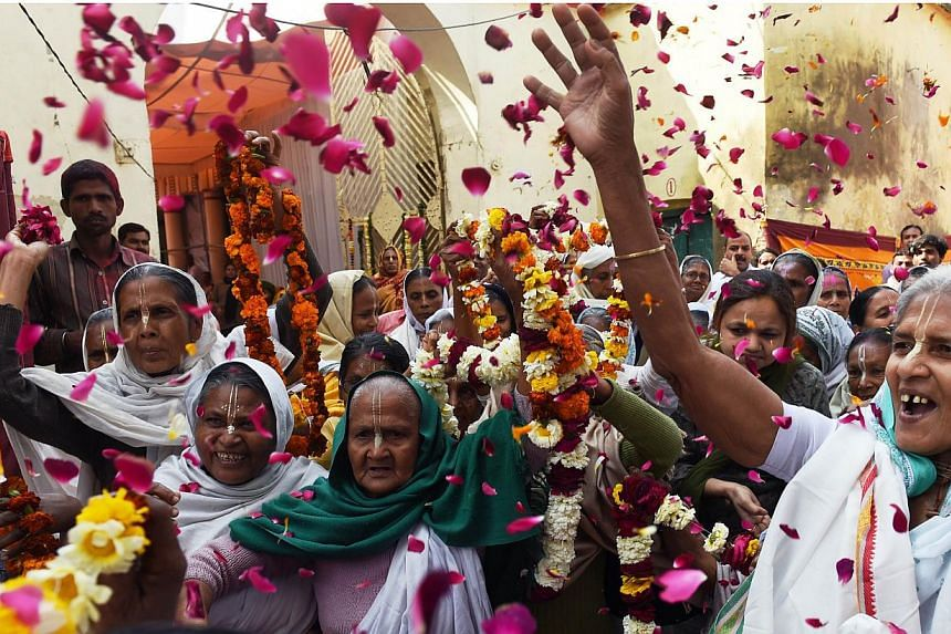 Indian widows throw petals as a sign of welcome on the arrival of Bindeshwar Pathak, founder of NGO Sulabh International which funds some Indian widows sheltering in ashrams, before playing Holi or the 'festival of colours' in Vindravan on March 3, 2