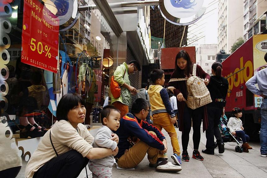 Tourists from mainland China resting outside a shop at a shopping district in Hong Kong on Feb 24, 2015. -- PHOTO: REUTERS