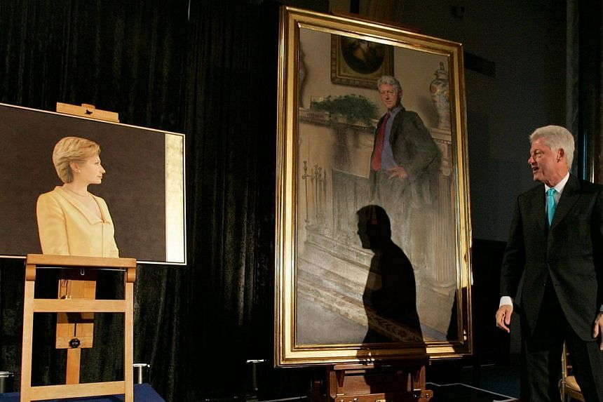 This April 24, 2006 file photo shows former US President Bill Clinton looking at his and his wife Hillary Clinton's portraits during an unveiling ceremony at the Smithsonian in Washington, DC. Mr Clinton's portrait, now in the National Portrait Galle