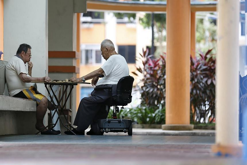 Two elderly man playing Chinese chess at a HDB block on Feb 23, 2015. During the first day of debate on Budget 2015, most MPs welcomed the largesse of new programmes such as the Silver Support Scheme to give the poorest elderly a basic pension. -- PH