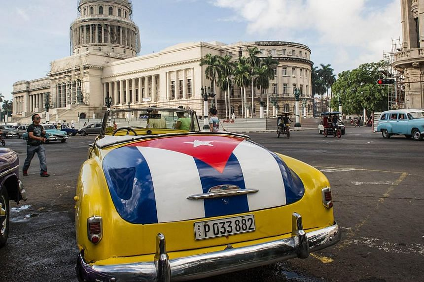 An old car with the Cuban flag painted on its trunk is seen near the Capitol of Havana, on Jan 7, 2015. -- PHOTO: AFP