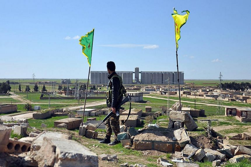 A Kurdish People's Protection Units fighter standing on top of a hill overlooking the the town of Tal Hamis, south-east of the city of Qamishli, on March 1, 2015. A former Royal Marine has become the first British fighter to be killed battling alongs