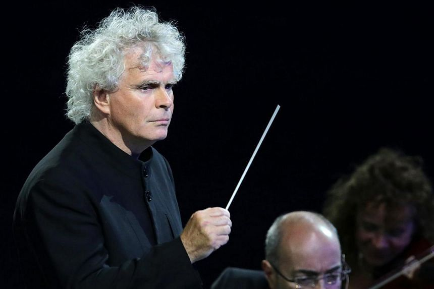 Rattle conducting the London Philharmonic Orchestra during the Opening Ceremony of the London 2012 Olympic Games at the Olympic Stadium in London, Britain. He is leaving the Berlin Philharmonic to lead the London Symphony Orchestra. -- PHOTO: EPA
