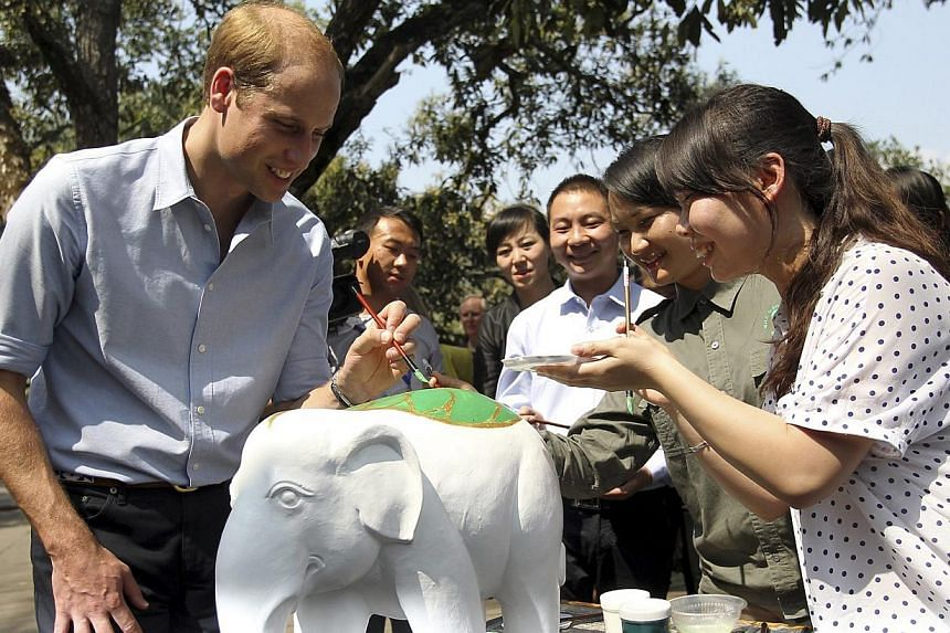 Britain's Prince William paints a leaf on the back of an elephant sculpture with volunteers as he visits the Wild Elephant Walkway in Xishuangbanna, Yunnan province, on March 4, 2015. -- PHOTO: REUTERS
