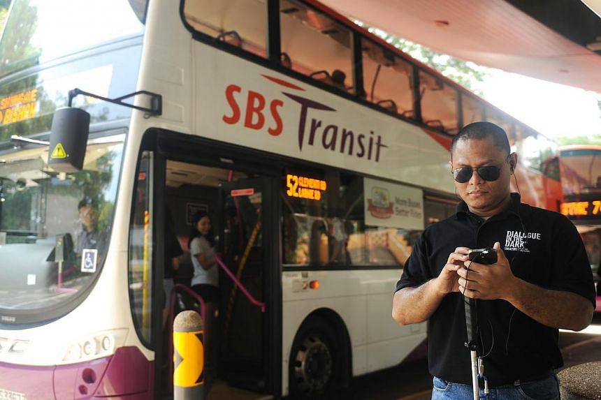 Mr Muhammad Hidayat, 26, a visually-impaired guide at NP's Dialogue in the Dark, tries out the TrAVEI (Travel Assistant for the Visually Impaired and the Elderly) app at a bus stop on March 4, 2015. -- ST PHOTO: TIFFANY GOH
