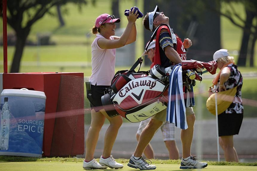 Lydia Ko of New Zealand jokes with her caddie after teeing off at the 11th hole during the Pro-am event on the eve of the HSBC Women's Champions on March 4, 2015. -- ST PHOTO: MARK CHEONG