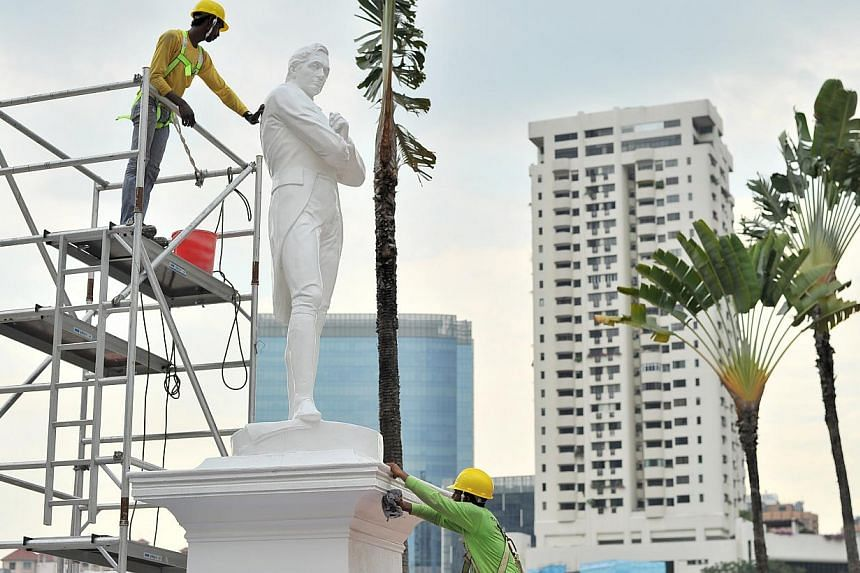 The statue of Sir Stamford Raffles being cleaned in 2014. Barricades and hoardings will soon be erected around several statues and landmarks along the Singapore River, to protect them from construction works. -- PHOTO: ST FILE