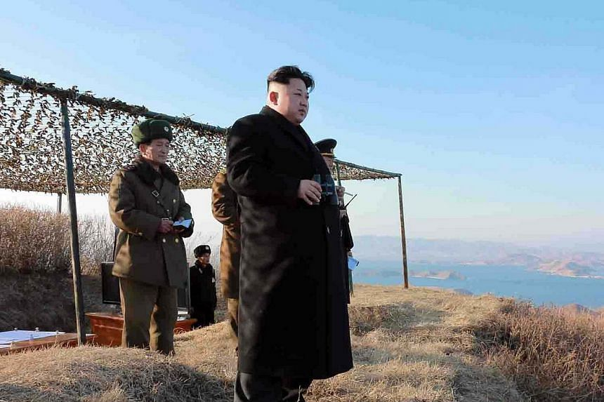 """This undated picture released from North Korea's official Korean Central News Agency (KCNA) on Feb 8, 2015 shows North Korean leader Kim Jong-Un (centre) inspecting the test-firing of a new type of """"anti-ship rocket"""" to be equipped at Korean People's"""