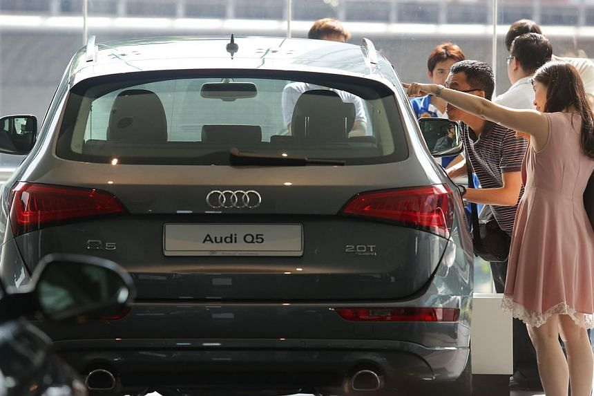 People looking at a car in the Audi showroom at Alexandra Road. COE premiums ended mostly higher in the latest tender on Wednesday, March 4, 2015. -- PHOTO: ST FILE