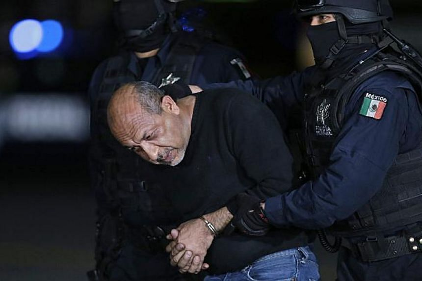 """Former primary school teacher Servando """"La Tuta"""" Gomez is escorted by police officers during a media conference about his arrest in Mexico City last week. Mexico captured its most wanted drug lord on Friday, delivering a boost to a government battere"""
