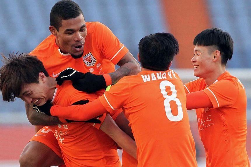 China's Shandong Luneng FC players celebrate after scoring a goal against South Korea's Jeonbuk Hyundai Motors during their AFC Champions League group E first round match at the Jinan Olympic Sports Centre in Jinan, northeast China's Shandong provinc