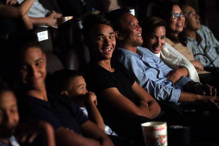 Together with his family, Fandi Ahmad, former national footballer and head coach of LionsXII, reacts during a video inspired by his life story during the launch of the SEA Games official album. -- ST PHOTO: NEO XIAOBIN