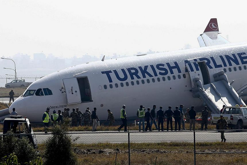 Nepalese emergency officials inspecting a Turkish Airlines plane after it skidded off the runway while landing at Tribhuvan International Airport in Kathmandu, Nepal on March 4, 2015.-- PHOTO: EPA