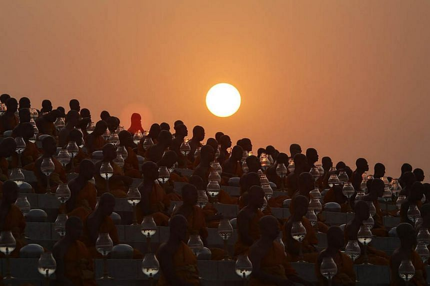 Buddhist monks prepare for an alms offering ceremony at the Wat Phra Dhammakaya temple in the north of Bangkok as the sun rises on Makha Bucha Day on March 4, 2015. -- PHOTO: REUTERS