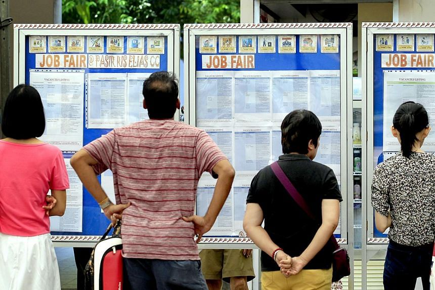 Visitors looking at the job listings displayed on boards at a job recruitment drive on May 3, 2014. -- PHOTO: ST FILE