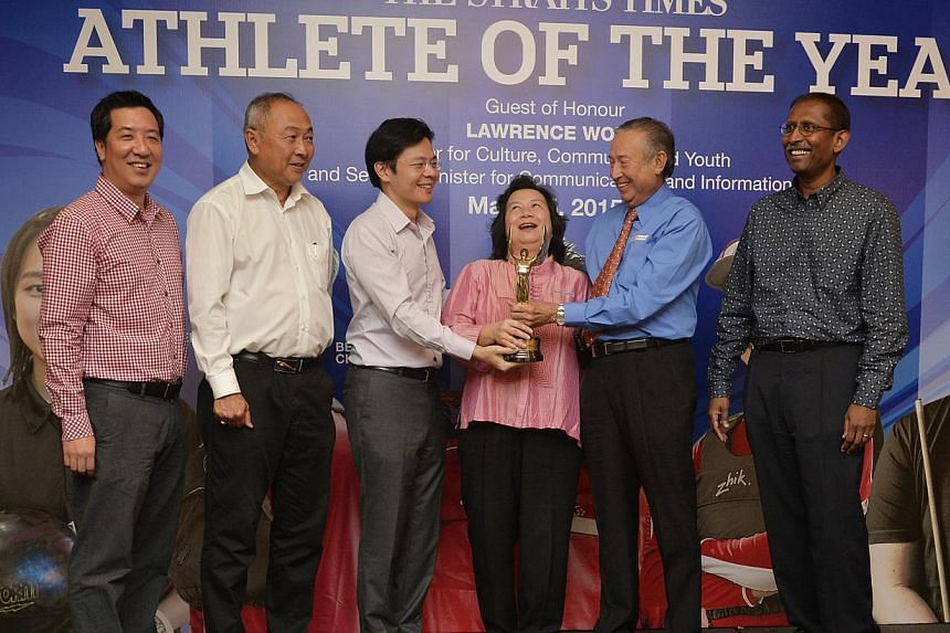 Joseph Schooling's parents May and Colin (centre, in pink and blue) receive his prize on his behalf during The Straits Times (ST) Athlete of the Year ceremony held at Raffles Hotel on March 5, 2015. Standing with them are (from left) ST sports editor