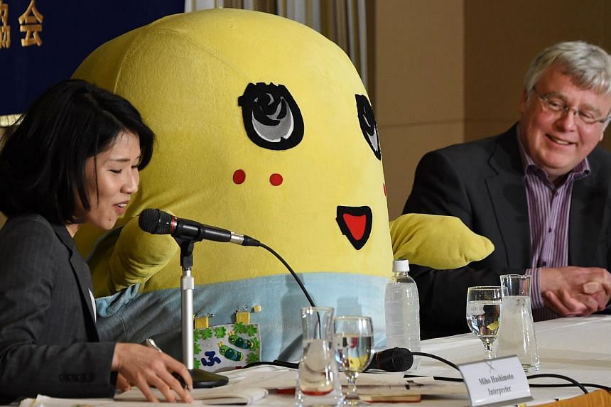 Pear fairy Funassyi (centre), the unofficial mascot of Funabashi City, a suburban city of Tokyo, answers questions during a press conference at the Foreign Correspondents' Club in Tokyo on March 5, 2015. -- PHOTO: AFP