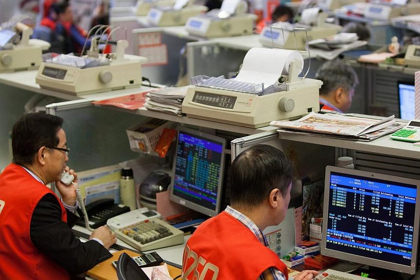Stock traders on the floor of the Hong Kong stock exchange on Feb 23, 2015. China plans on linking up the Shenzhen and Hong Kong stock exchanges on a trial basis as part of its financial sector reform. -- PHOTO: EPA