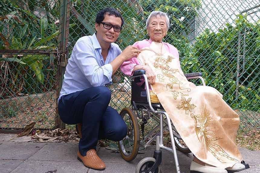 Artist-architect Randy Chan with Madam Maggie Kwek and her cheongsam dating back to the 1940s. -- ST PHOTO: DANIEL NEO