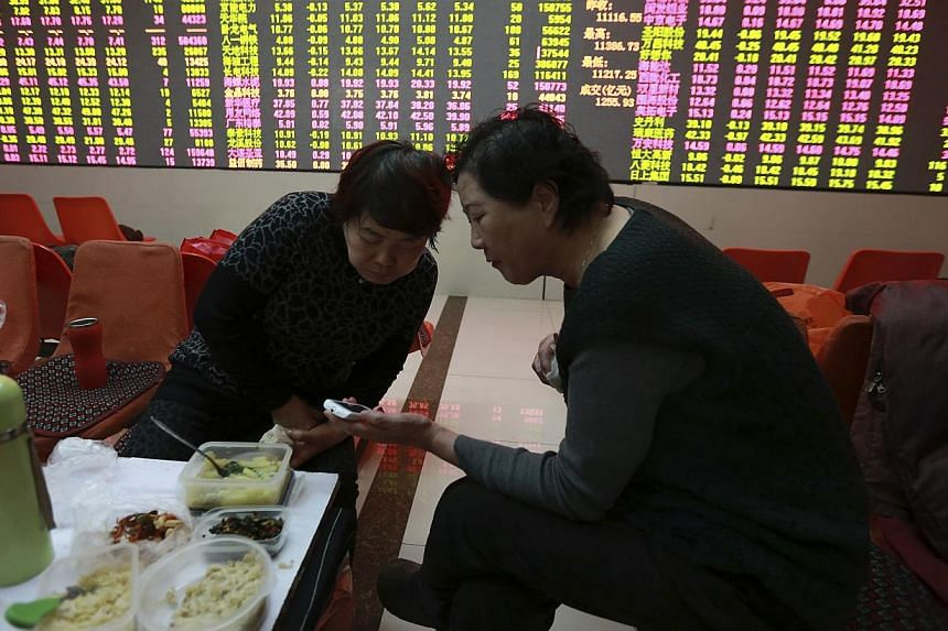 Investors look at a mobile phone as they have lunch in front of an electronic board showing stock information at a brokerage house in Shenyang, Liaoning province onFeb 5, 2015. China's stocks fell, erasing the benchmark index's gain for the yea