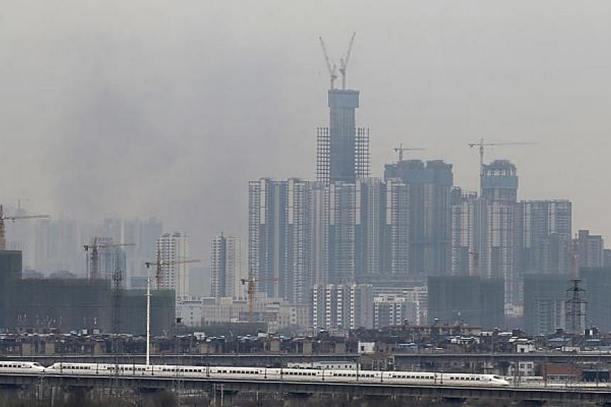 A bullet train runs past buildings under construction in Wuhan, Hubei province, on Feb 28, 2015.