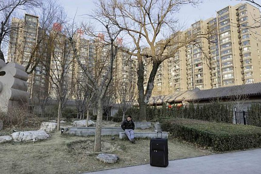 A man sits near apartment blocks in central Beijing, on Dec 22, 2014.