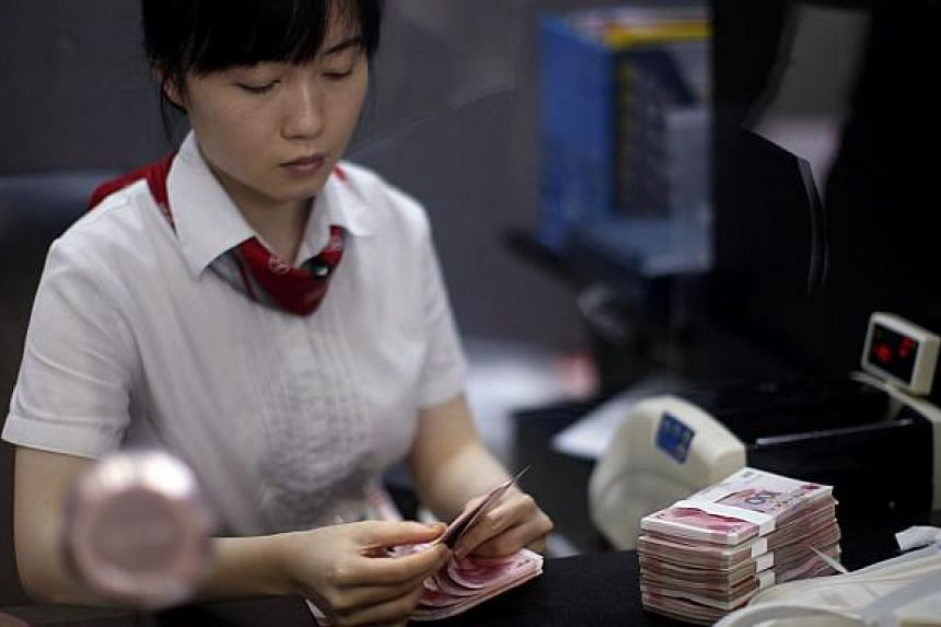 An employee of the Industrial and Commercial Bank of China Ltd (ICBC) counts money at one of the bank's branches on Sept 24, 2014.
