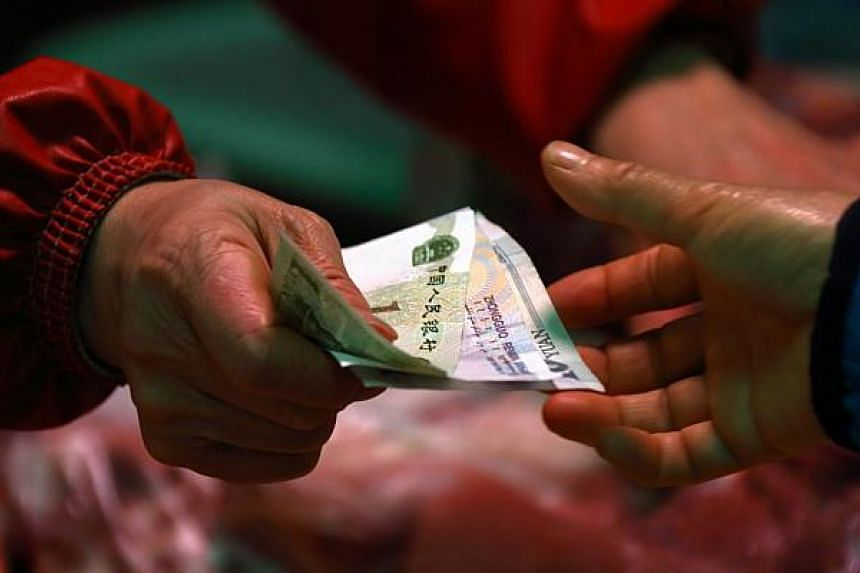 A woman holds Chinese yuan banknotes as she buys pork at a market stall in Beijing, China, on March 4, 2015.