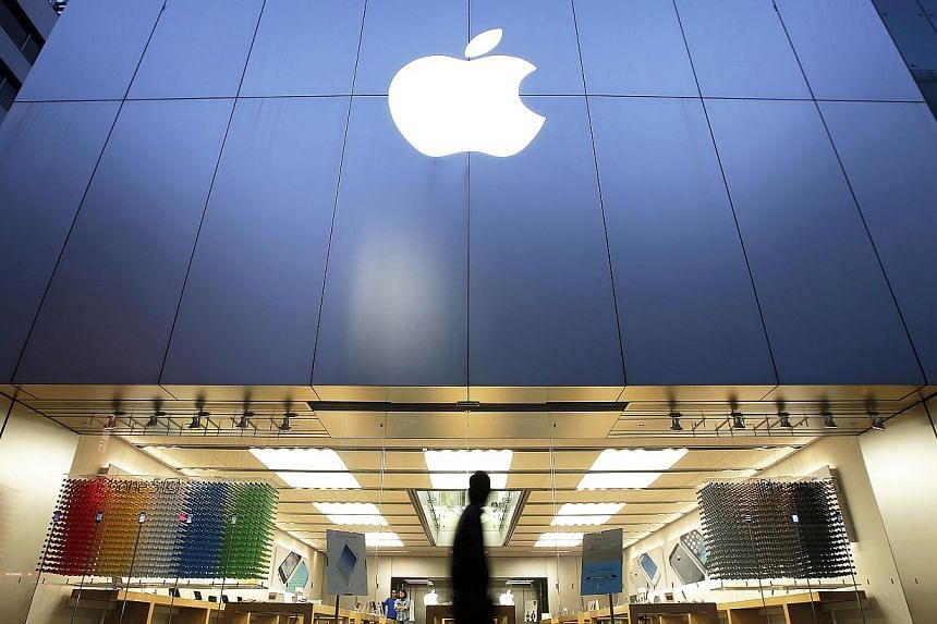 A man walks past an Apple store in the Ginza district of Tokyo, Japan. The company, which has seen stagnating iPad sales, will delay the start of manufacturing for a larger-screened version of the tablet. -- PHOTO: BLOOMBERG